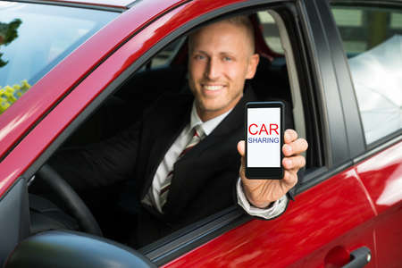 Happy Businessman Sitting In Car Showing Cellphone With Car Sharing Text On Screen