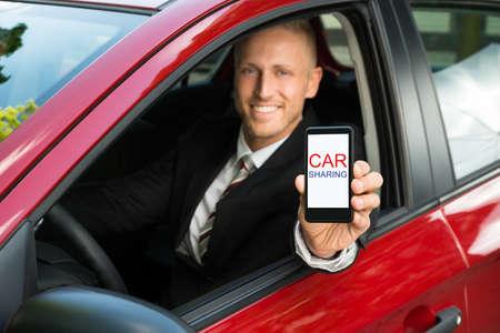 uomo rosso: Imprenditore Felice seduto in macchina Mostrando Cellulare Con Car Sharing Testo sullo schermo