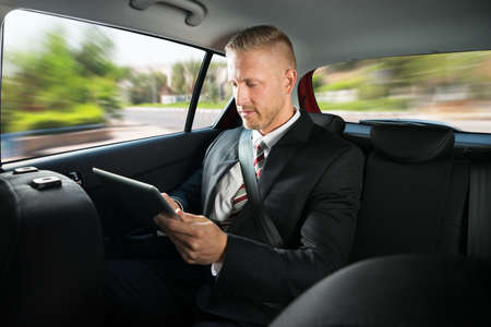 business protection: Portrait Of A Businessman Using Digital Tablet While Travelling In A Car