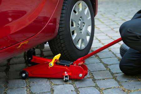 auto lift: Car Lifted With Red Hydraulic Floor Jack For Repairing