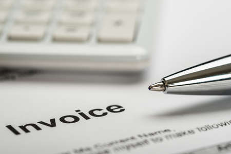 Close-up Of Pen With Calculator Over Invoice Paper
