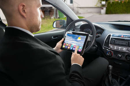 using tablet: Close-up Of A Businessman Sitting In Car Using Digital Tablet Stock Photo