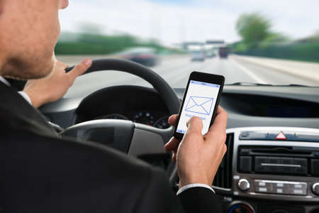 drive: Close-up Of A Man Holding Cellphone With Message Notification While Driving Car