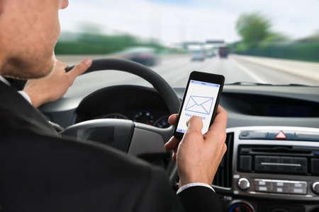 hombre manejando: Primer plano de un hombre con el teléfono celular con la notificación de mensajes durante la conducción de coches