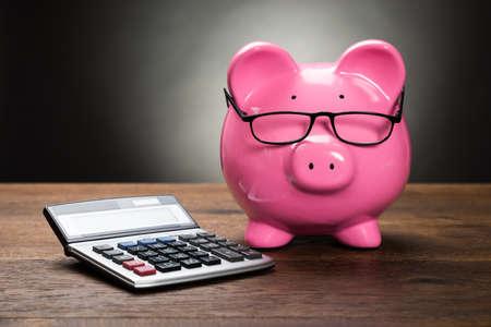 prosperidad: Hucha rosada con la calculadora en mesa de madera