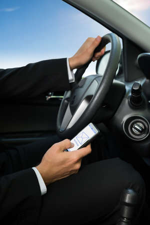 Close-up Of A Man Holding Cellphone While Driving Car photo