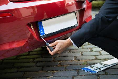 Man Platzieren New Leere weiße Nummernschild auf seinem roten Auto