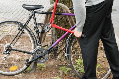 ladron: Ladrón tratando de romper el candado de bicicleta con los alicates largos Foto de archivo