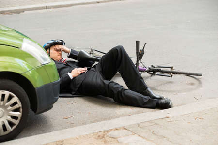 the unconscious: Unconscious Male Cyclist Lying On Road After Road Accident