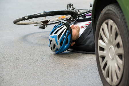speed car: Unconscious Male Cyclist Lying On Street After Road Accident Stock Photo