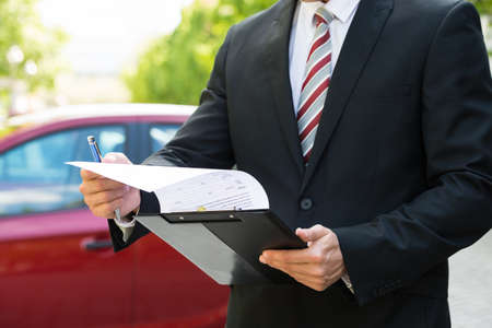 Close-up Of A Man Standing In Front Of Car Holding Clipboard In His Hand