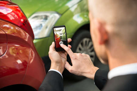 Male Driver Photographing With His Cellphone After Traffic Collision