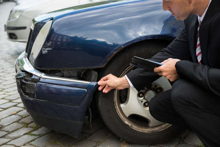 damaged car: Insurance Agent Inspecting Car Involved In Accident