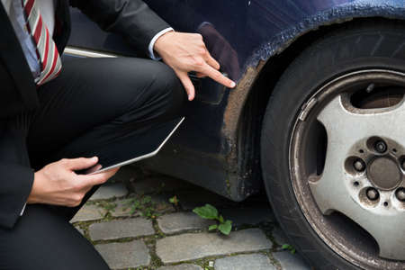 accident: Insurance Agent Holding Digital Tablet Examining Car Damaged After Accident