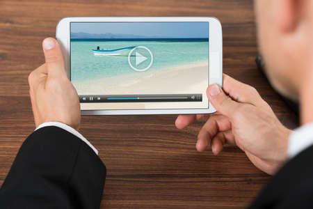 viendo television: Primer De Empresario V�deo Visualizaci�n por tel�fono m�vil en la oficina Foto de archivo
