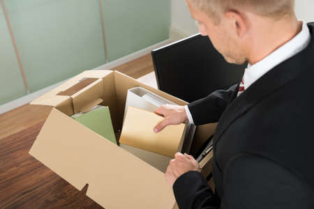 unemployed: Close-up Of A Businessman Packing Files In Cardboard Box At Office