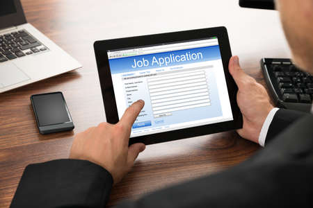 mobile business: Close-up Of Businessman Filling Online Job Application On Digital Tablet Stock Photo