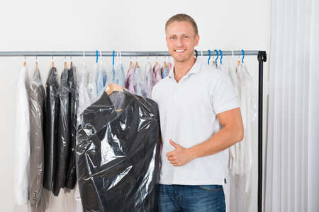 dry suit: Young Happy Man Standing With Coat In Dry Cleaning Store Stock Photo