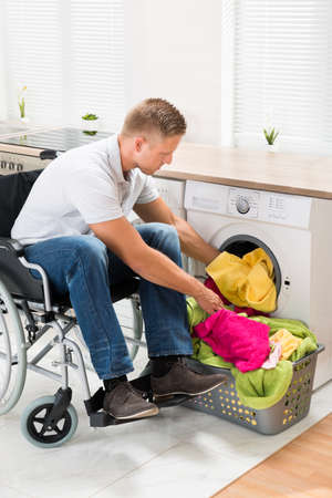 household accident: Young Disabled Man On Wheelchair Putting Towels Into The Washing Machine