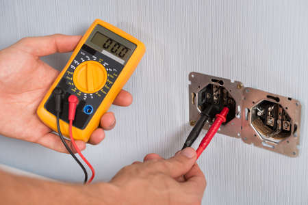 voltage: Close-up Of Person Hand Checking Socket Voltage With Multimeter