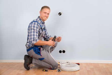 stripping: Young Electrician Stripping Wire With Plier In House Stock Photo