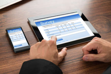 control de calidad: Primer plano de un empresario Llenar formulario de encuesta en línea sobre la tableta digital y teléfono móvil