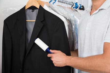 糸くずローラーが付いているコートのほこりを除去する人の手のクローズ アップ