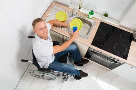 silla de rueda: Vista elevada Del Hombre Feliz En silla de ruedas con platos de esponja de lavado en el fregadero