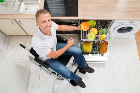handicapped person: Young Happy Disabled Man On Wheelchair Arranging Plate In Dish Rack