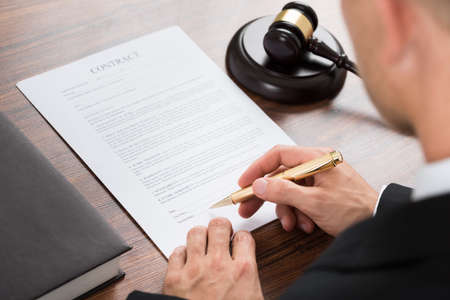 signing authority: Close-up Of Judge Signing Contract Paper At Desk In Courthouse