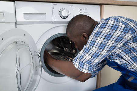 Close-up Of Young African Technician Repairing Washing Machine