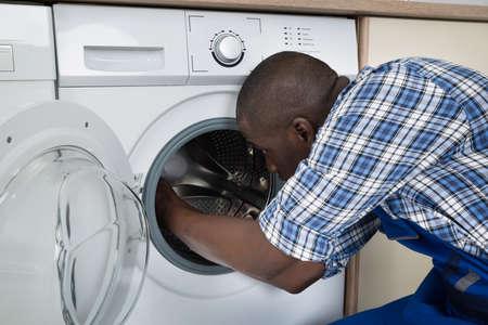 Close-up Of Young African Technician Repairing Washing Machine photo