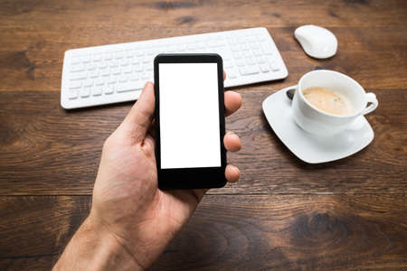 hand phone: Close-up Of Person Hand Holding Mobile Phone With Cup Of Tea On Desk Stock Photo