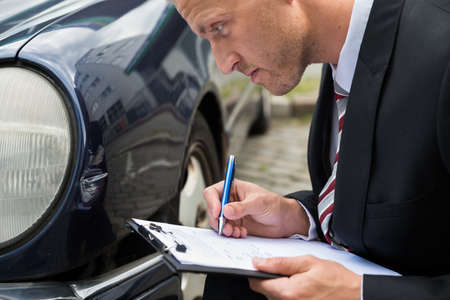 automobile insurance: Close-up Of A Man Filling Insurance Form Near Damaged Car Stock Photo