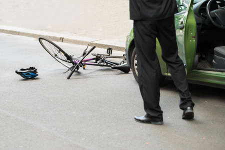 crash helmet: Close-up Of Male Driver After Collision With Bicycle On Road