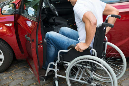 Wheel chair: Close-up Of A Disabled Man In Wheelchair Getting In His Car