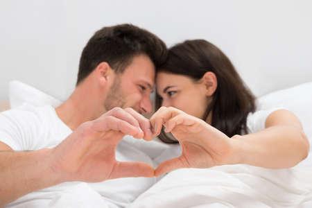 ロマンス: 手でハートの形を形成するベッドに横になっているカップル 写真素材