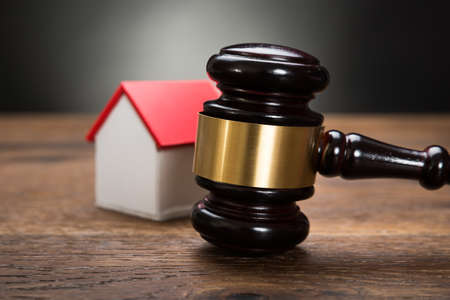 auction: Close-up Of House Model With Gavel On Wooden Table Stock Photo