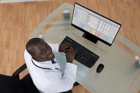 teclado de computadora: Opinión de alto ángulo del teclado Feliz africano joven doctor de sexo masculino que pulsa en el ordenador Foto de archivo