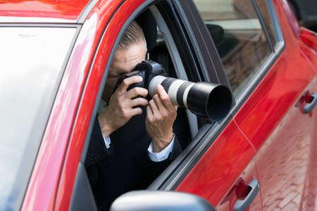 자동차에서 SLR 카메라와 함께 남성 드라이버 사진 촬영의 근접