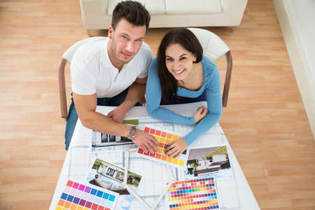 home plans: High Angle View Of Young Couple Choosing Color From Swatch