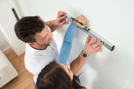 two level house: Happy Couple Marking With Pencil On Wall With Level In House Stock Photo