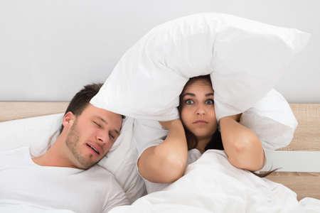 mujer en la cama: Mujer irritada tap�ndose los o�dos con la almohada Si bien el hombre que ronca en la cama en casa Foto de archivo