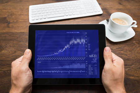 Close-up Of Person Hands With Digital Tablet Showing Graph At Desk photo
