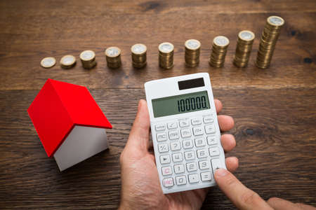Businessman Using Calculator With House Model And Stack Of Coins On Desk