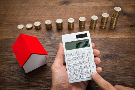 impuestos: Hombre de negocios usando la calculadora Con La Casa Modelo Y Pila De Monedas En El Escritorio