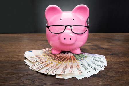 coinbank: Primer Plano De Una Hucha En billetes en euros Con Anteojos