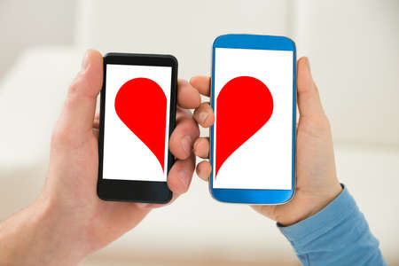 Close-up Of A Couple's Hand Holding Cellphone With Half Red Heart Symbol