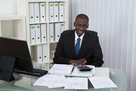 empresario: Hombre de negocios africano joven Cálculo de Cuentas en la oficina