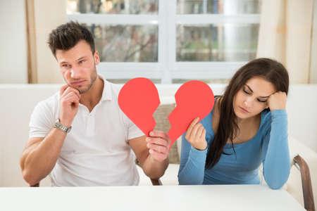 divorcio: Retrato De Una Pareja triste Sentado en el coraz�n Presidente Holding Red Broken